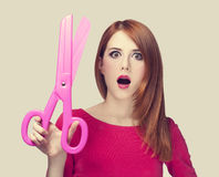 Redhead girl with big scissors Stock Photography