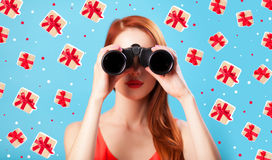 Redhead girl with binocular. On blue background Royalty Free Stock Image