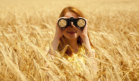Redhead girl with binocular at wheat field. stock images