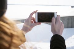Redhead girl in a black hat and a black coat on a Sunny winter day taking pictures of themselves on the phone. Selfie Royalty Free Stock Photography