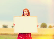 Redhead girl with blackboard Royalty Free Stock Images