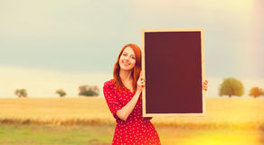 Redhead girl with blackboard. At wheat field Royalty Free Stock Photography