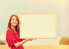 Redhead girl with blackboard. At wheat field Royalty Free Stock Image
