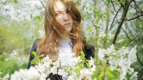 Redhead girl in blooming flowers stock video footage
