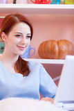 Redhead girl in blue blouse with computer Stock Photo