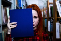 Redhead girl with blue book in a library. Beautiful redhead girl in red shirt stands with blue book in library near bookshelfs royalty free stock photography