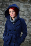 Redhead girl in blue coat Stock Photography