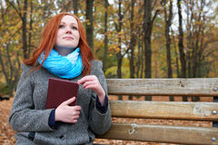 Redhead girl with book sit on a bench in city park, fall season Royalty Free Stock Images