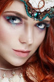 Redhead girl with bright makeup and big lashes. Mysterious fairy woman with red hair. Big eyes and colored shadows, long lashes. Sexy look, pure skin care Royalty Free Stock Images