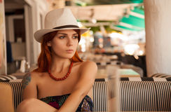 Redhead girl in casual outfit. Portrait of a redhead girl in casual outfit in bar royalty free stock image