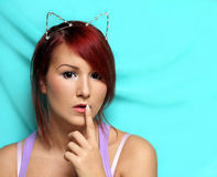 Redhead girl with cat ears holding her finger at the lips Royalty Free Stock Images