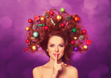 Redhead girl with christmas toys. Beautiful redhead girl with christmas toys and canes in hair on violet background stock photography