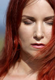 Redhead girl with closed eyes enjoying sunlight and wind at the Royalty Free Stock Photo