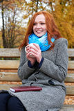 Redhead girl with cup of tea sit on a bench in city park, fall season Stock Photos