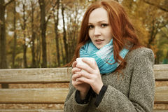 Redhead girl with cup of tea sit on bench in city park, fall season Royalty Free Stock Photography