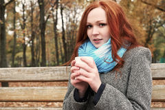 Redhead girl with cup of tea sit on a bench in city park, fall season Stock Images