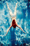 Redhead girl dive in pool shot from above stock photo