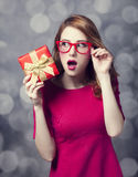 Redhead girl in dress with present box. Stock Photos