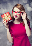 Redhead girl in dress with present box. Stock Images