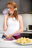 Redhead girl drinking in kitchen Royalty Free Stock Photography