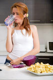 Redhead girl drinking in kitchen Stock Photo