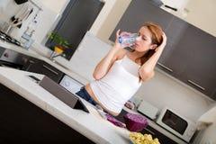 Redhead girl drinking in kitchen Stock Photo