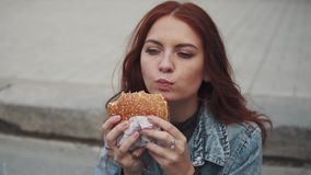 Redhead girl enjoy tasty bites delicious sandwich and smiles slyly. 20s. Girls eating fast food sitting on steps in city stock video footage