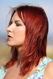 Redhead girl enjoying summer sunlight and calm wind at the sea Royalty Free Stock Images