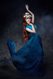 Redhead girl fabulous look, blue long dress, bright makeup and big eyelashes. Mysterious fairy woman with red hair. Big eyes. And colored shadows, long lashes royalty free stock photo