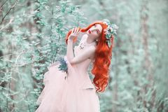 Redhead girl in fantasy world with very long hair in pink dress on spring background. A beautiful girl with flower bouquet in royalty free stock image