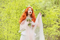 Redhead girl in fantasy world with very long hair in pink dress on spring background. A beautiful girl with flower bouquet in stock photo