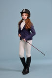 Redhead girl with freckles jockey. Redhead girl with freckles in riding clothes and helmet on a light background, the concept of a jockey Royalty Free Stock Photo