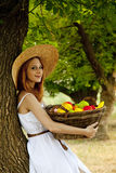 Redhead girl with fruit at garden. Stock Image