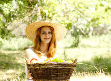 Redhead girl with fruits in basket Stock Photography