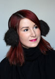 Redhead girl in fur ear muffs Royalty Free Stock Photography