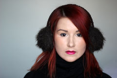 Redhead girl in fur ear muffs Royalty Free Stock Images
