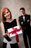 Redhead girl with a gift box and man behind her Stock Photos