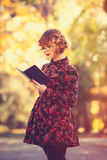Redhead girl in glasses with book Stock Image