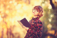 Redhead girl in glasses with book Stock Photography