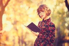 Redhead girl in glasses with book Royalty Free Stock Image