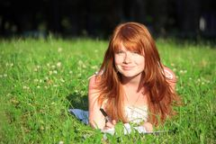 Redhead girl in the grass Royalty Free Stock Photos