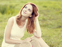 Redhead girl at green grass at village outdoor. Royalty Free Stock Photo