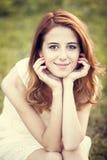 Redhead girl at green grass at village outdoor. Royalty Free Stock Image