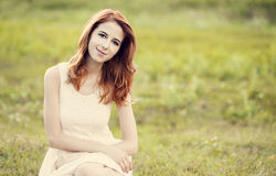 Redhead girl at green grass at village outdoor. Royalty Free Stock Images