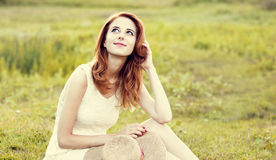 Redhead girl at green grass at village outdoor. Stock Images