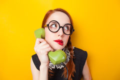Redhead girl with green phone Royalty Free Stock Images