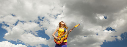 Redhead girl with guitar at outdoor. Stock Photos