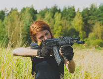 Redhead girl with a gun in his hand Royalty Free Stock Images