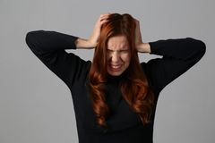 The redhead girl has an awful headache migraine at gray background her home. ! stock photography