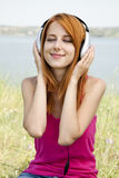Redhead girl with headphone Stock Images